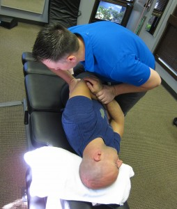 Dr. DeRoche performs a chiropractic adjustment on a patient.