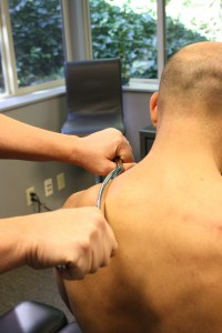 Dr. Eric DeRoche performs instrument-assisted soft tissue treatment on a patient